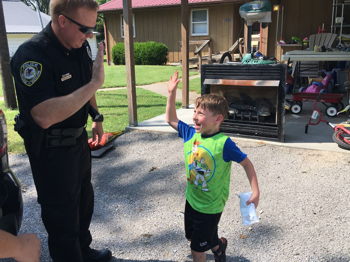 Police officers hand out ice cream to boost morale after flooding