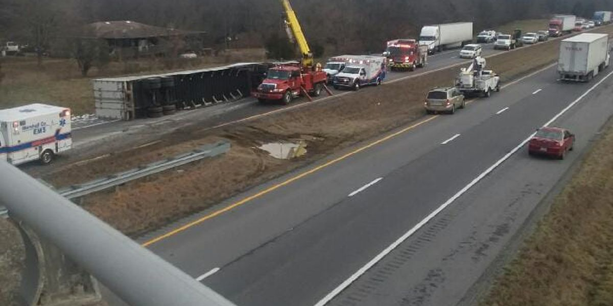 Power crew uses equipment to lift overturned semi blocking traffic on southbound I-69