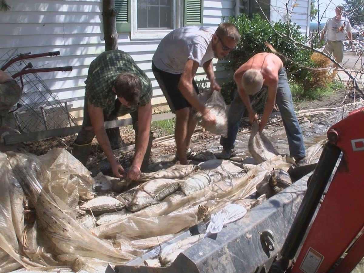 Volunteers help clean up sandbags in McClure, Ill.