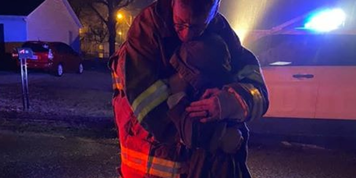 Firefighter comforts young girl after house fire