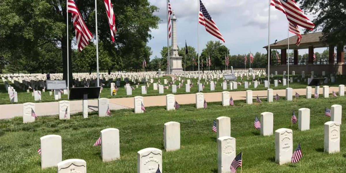Staff put flags up at each grave at Mound City National Cemetery