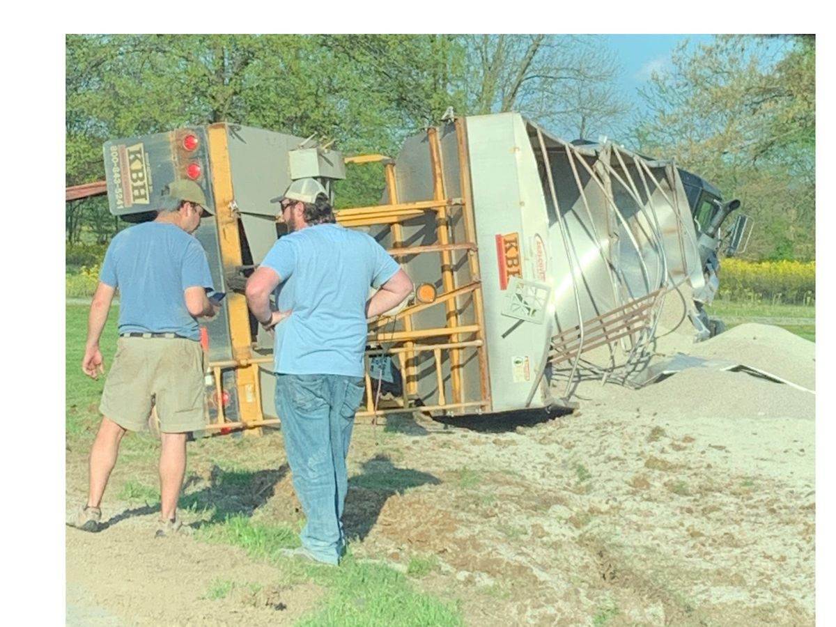 Semi hauling fertilizer overturns into yard