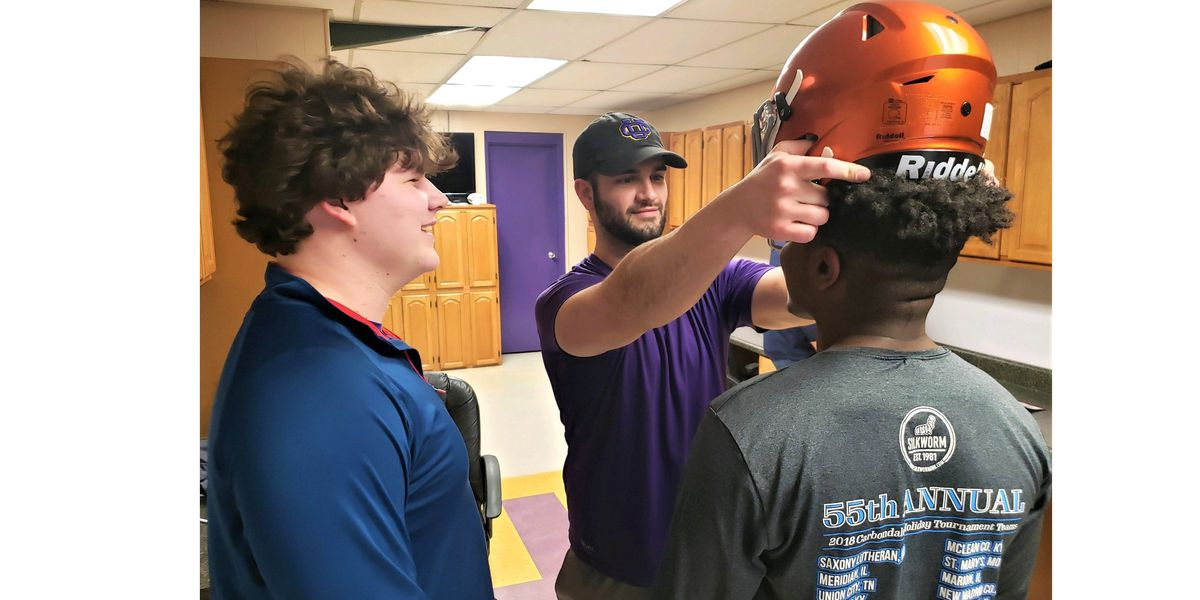 High school football players fitted for new, safer helmets