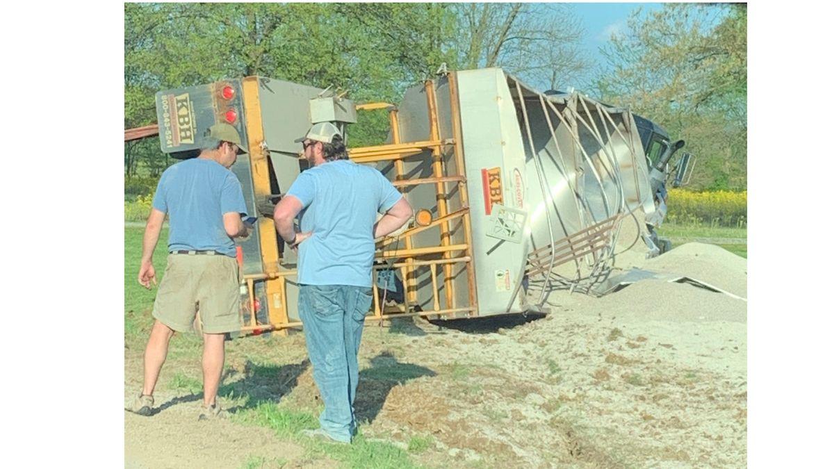 Semi hauling fertilizer overturns into yard